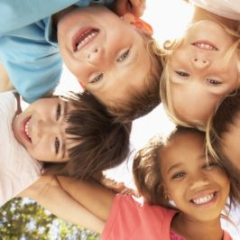 An Image of five smiling kids with linked arms looking down the camera, the hero image for the Therapy Pro for Kids brand