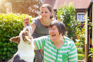 An image of a woman with a disability and a second woman rewarding a dog with a treat