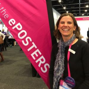 Therapy Pro OT Sandra stands beside the ePoster banner at the 2019 OT conference in Sydney