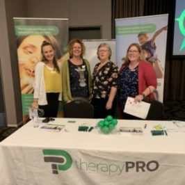 Four therapists from the Townsville team stand together at a table at a networking event