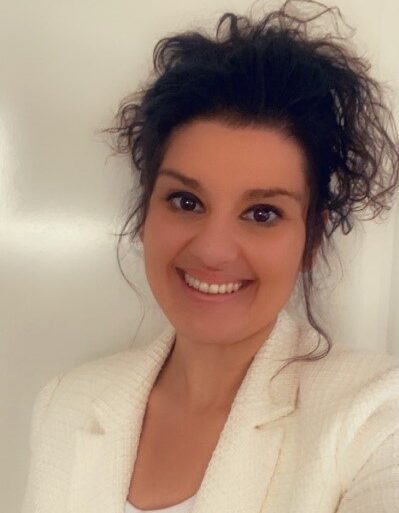 Daniela Guzzardi smiling at the camera in a white suit jacket