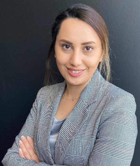 An image of Sahar Fattahi provisional psychologist smiling at the camera with a grey suit jacket, folding her arms