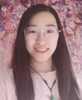 A picture of Olivia Sun, who has long dark hair, is wearing glasses and smiling at the camera