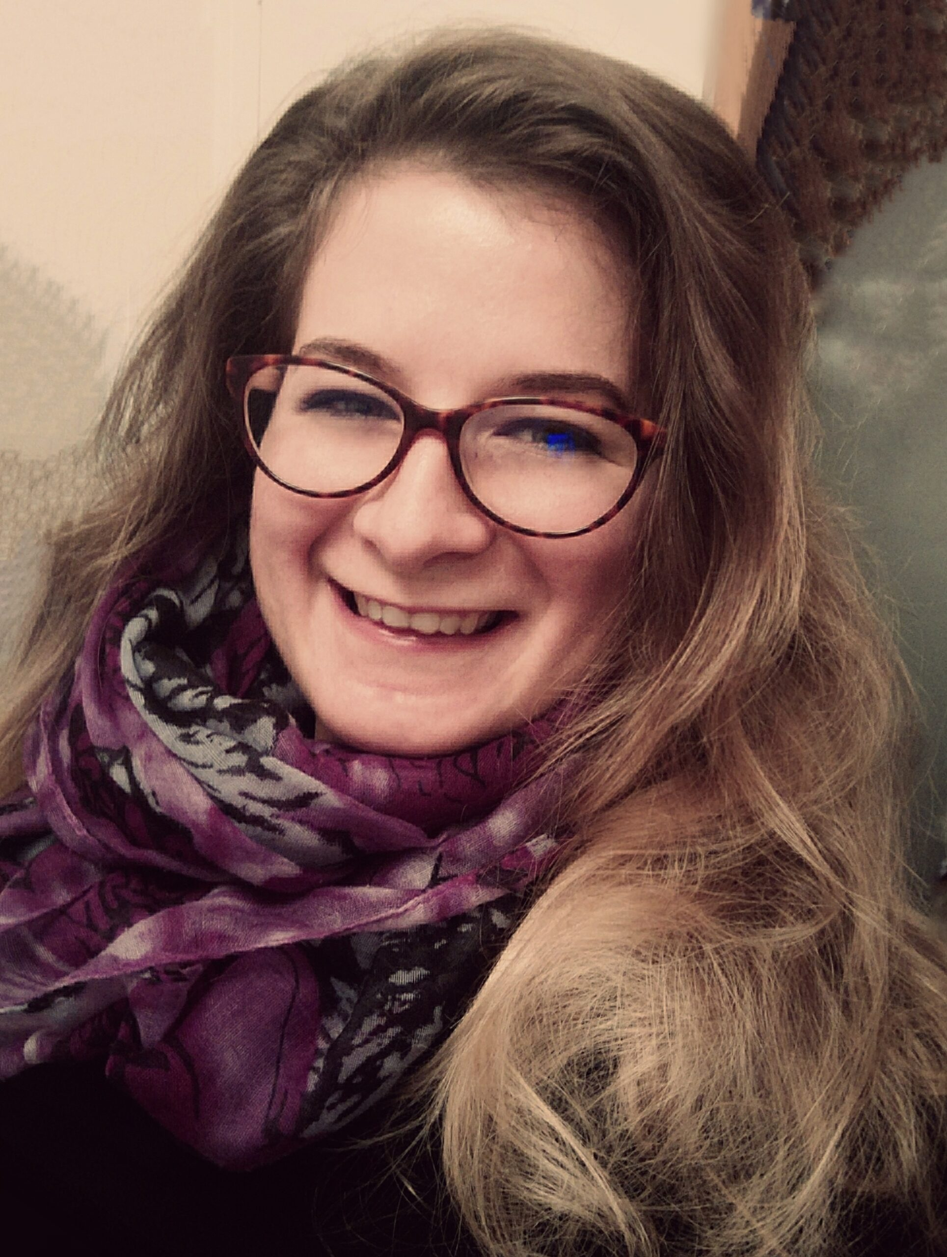 A photo of Zsuzsanna who smiles at the camera, she wears glasses, a scarf and hand long light brown hair