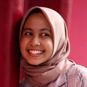 A woman wearing a pink headscarf and shirt, smiles, standing against a wall with stripes of different pinks. Photo by Lek Nikto on Unsplash
