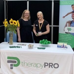 Maree and Aninslee are at an exhibition booth, they stand behind a display table that has therapy pro balls and flyers on it and a large bunch of sunflowers. There are two therapy pro banners on either side of the people.