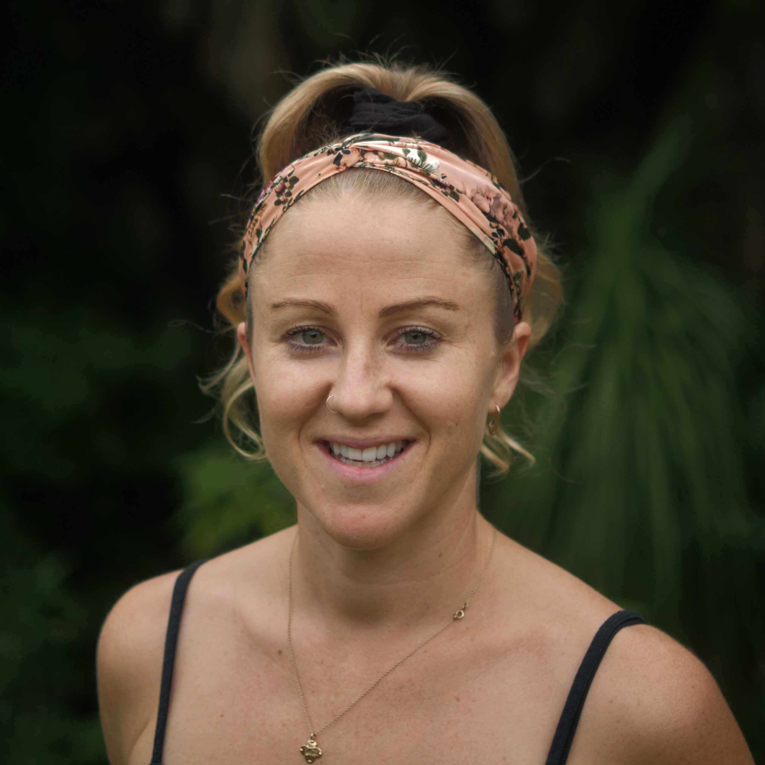 michelle hammond smiles at the camera. She is standing outside in the gardern and has her hair tied up and a head scarf on.