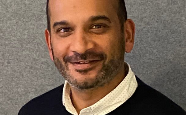 a man stands against a grey background and smiles at the camera, he is wearing a white business shirt and navy blue jumper