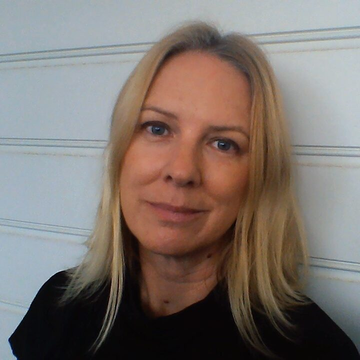 a woman with blonde hair and a dark jumper on smiles at the camera against a white background