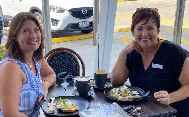 Two women sit in a cafe having breakfast and coffee, they are happy and smile at the camera