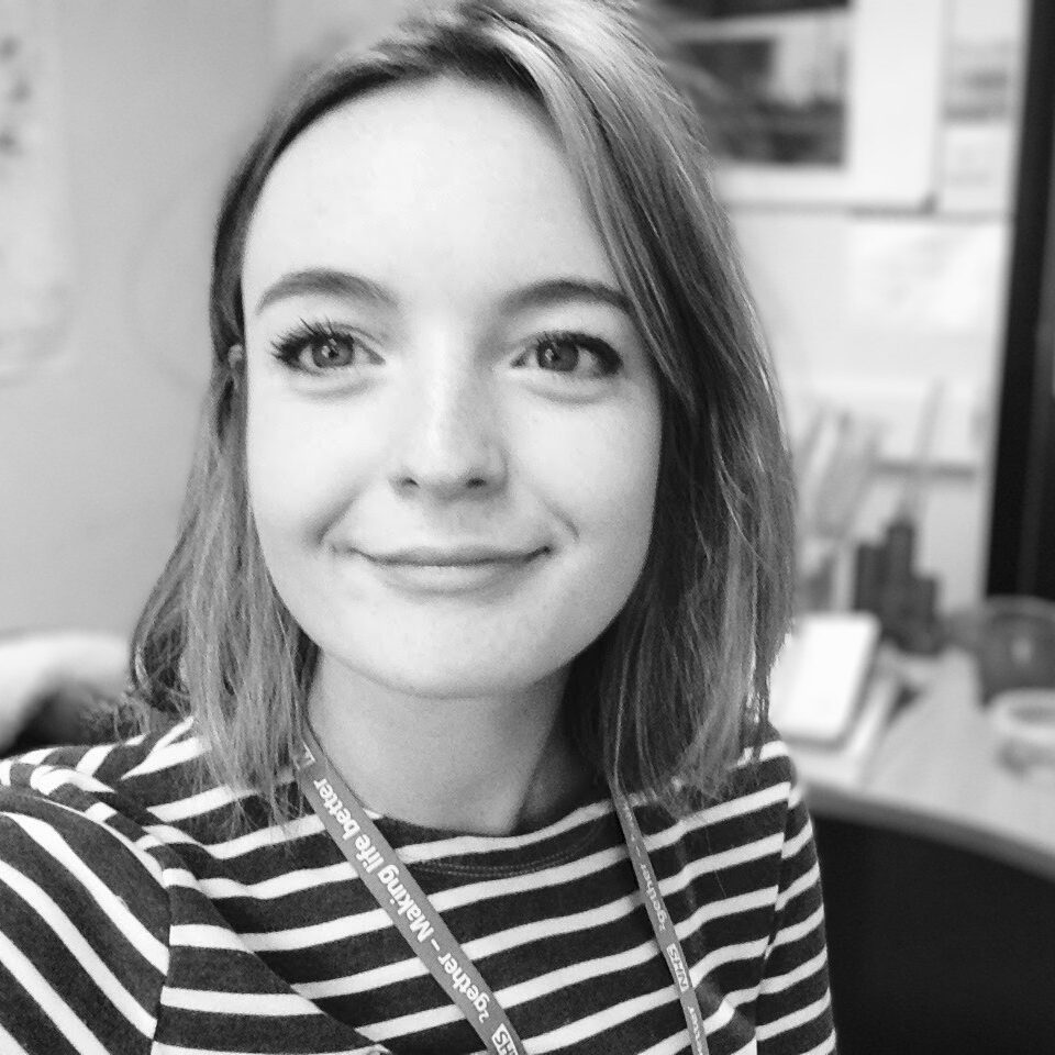Martha smiles at the camera, she has short hair and a striped top