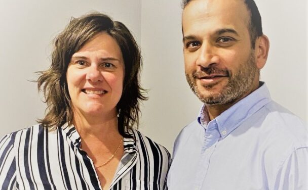 karen and chirag stand together, they smile at the camera in front of a white background, photo credit Sue Fothergill