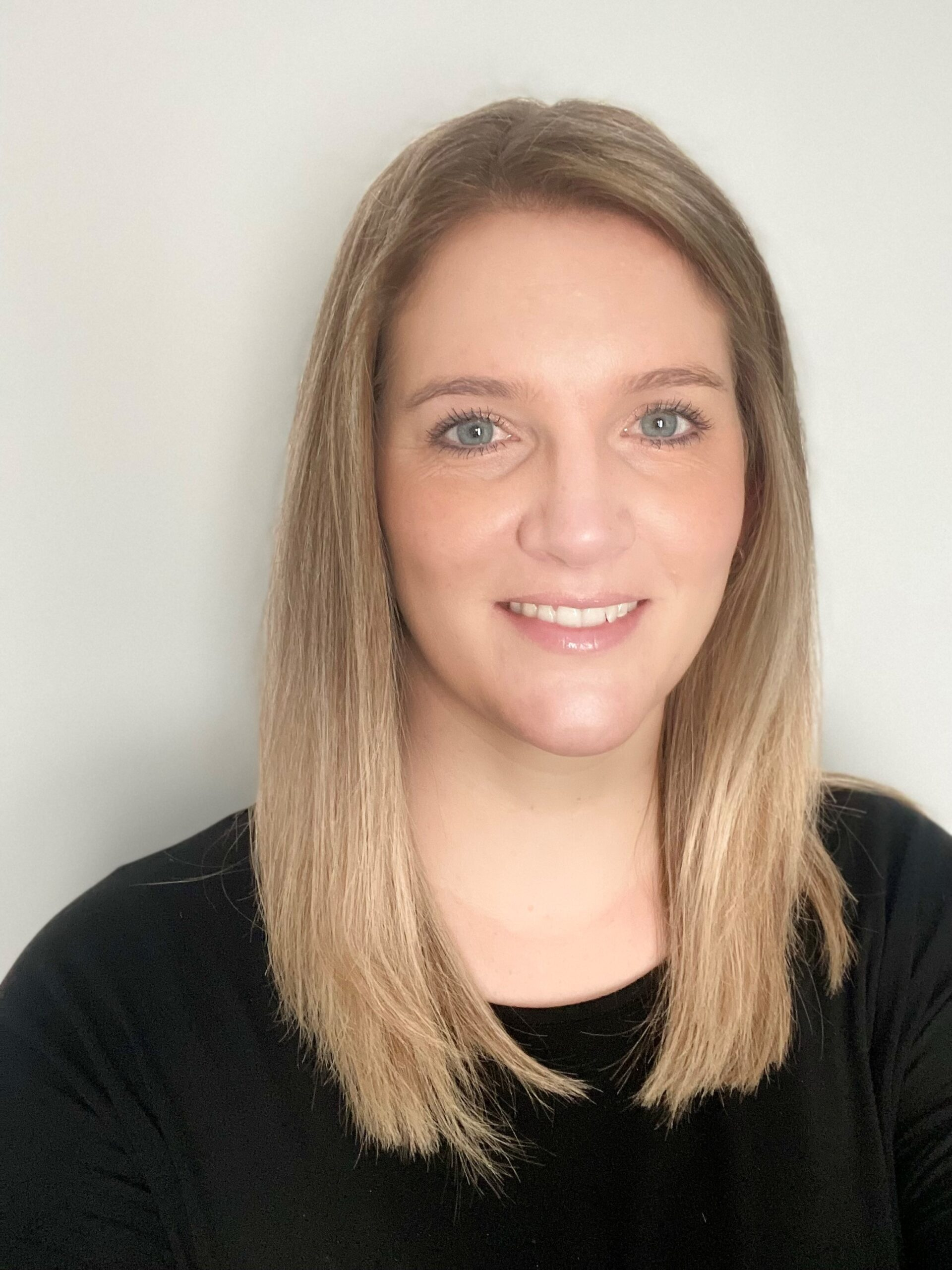 A professional picture of Lauren who smiles at the camera, she is happy to work at therapy pro
